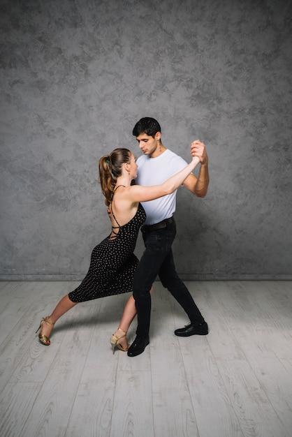 Jeunes partenaires de danse dansant le tango Photo gratuit