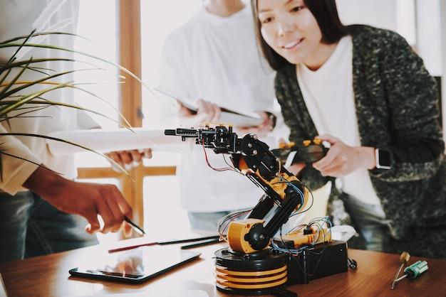Jeunes spécialistes avec robot au travail. Photo Premium