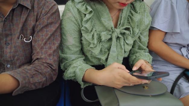 Les Jeunes Utilisant Le Téléphone Mobile Dans Le Métro Public. Mode De Vie De La Ville Urbaine Et Navettage Dans Le Concept De L'asie. Photo Premium