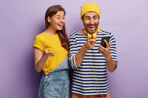 Les Jeunes Utilisateurs Optimistes De La Technologie Intelligente, Se Sentent Bien Après Une Mise à Jour Réussie Du Téléphone Portable, Regardent L'écran, Consultez L'article Photo gratuit