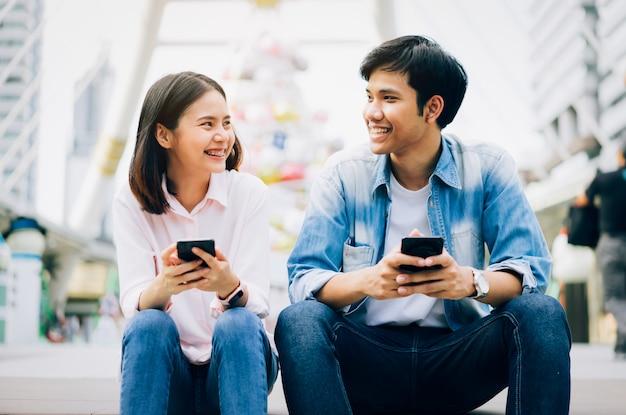 Les jeunes utilisent un smartphone et sourient lorsqu'ils sont assis sur leur temps libre. Photo Premium