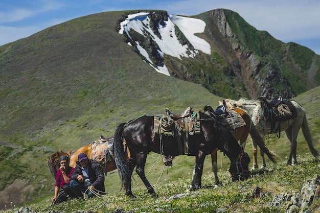 Jeunes Et Vieux Cavaliers à Pied Trois Chevaux à Flanc De Montagne Dans Le District D'ulagansky De La République De L'altaï, Russie Photo Premium
