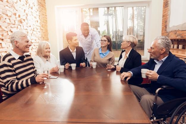 Jeunes et vieux sont assis ensemble dans la salle du foyer Photo Premium
