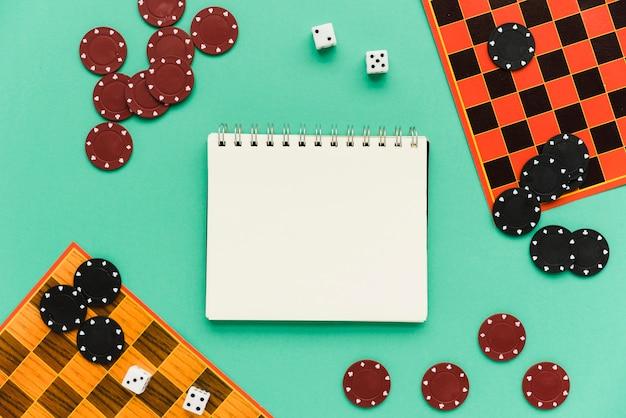 Jeux de société avec vue de dessus avec le bloc-notes de maquette Photo gratuit