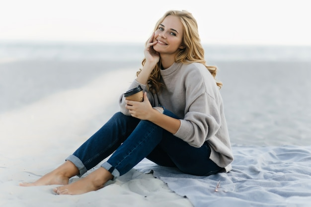 Jocund Femme En Jeans Assis à La Plage Avec Une Tasse De Café. Jolie Femme Aveugle Posant Dans Le Sable En Journée D'automne. Photo gratuit