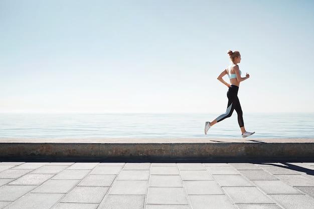 Jogging Jeune Femme Qui Court Sur Le Rivage Photo gratuit
