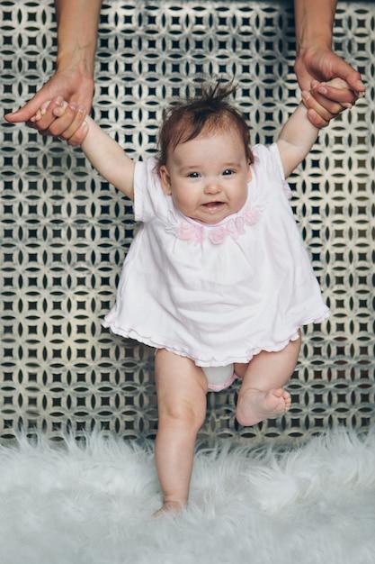 Joli bébé apprend à marcher et à faire ses premiers pas. maman lui tient la main. les pieds de l'enfant se bouchent, copient l'espace Photo Premium