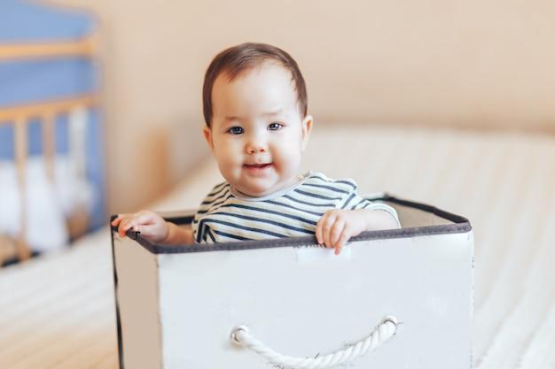 Joli bébé bébé garçon ou fille assis à l'intérieur d'une boîte dans l'appartement Photo Premium