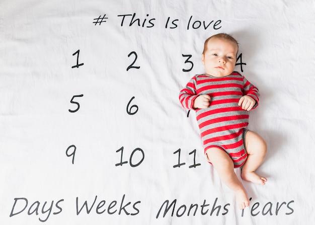 Joli bébé sur le corps rayé avec calendrier Photo gratuit