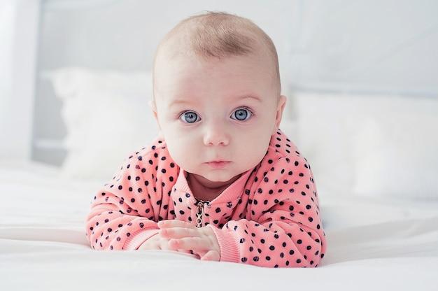 Joli bébé sur le lit blanc Photo Premium