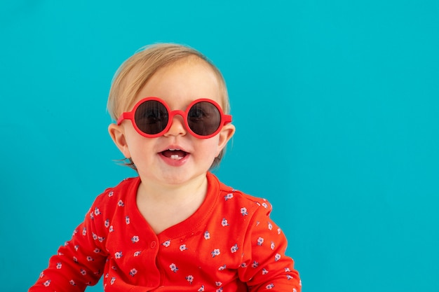 Joli bébé à lunettes de soleil rouges sourire Photo Premium