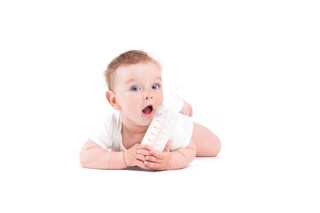 Joli Bébé Mignon En Chemise Blanche Se Trouve Sur Le Ventre Avec Une Bouteille De Lait Photo Premium