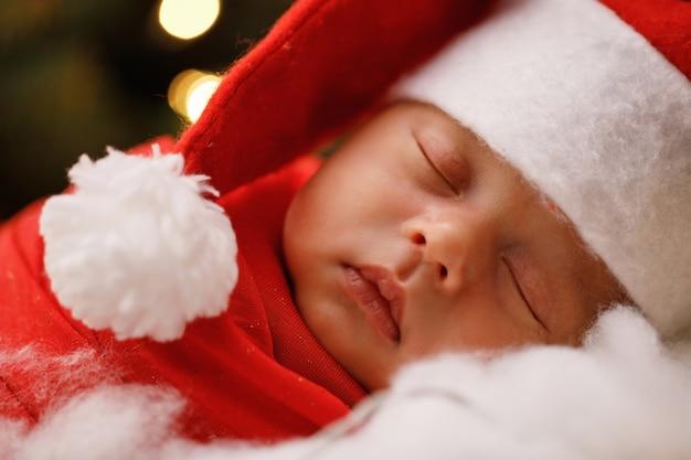 Joli bébé nouveau-né portant le chapeau du père noël dort Photo Premium