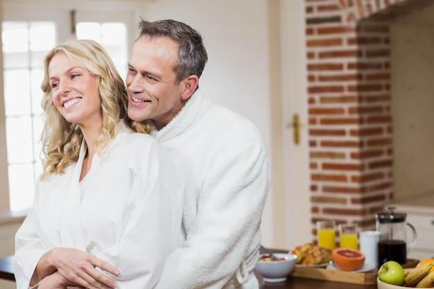 Joli couple câlin dans des peignoirs dans la cuisine Photo Premium