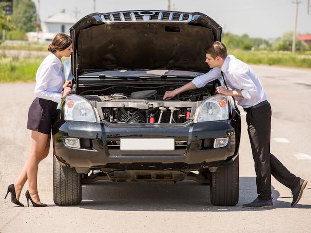 Joli couple essaie de réparer leur voiture en utilisant le manuel. Photo Premium