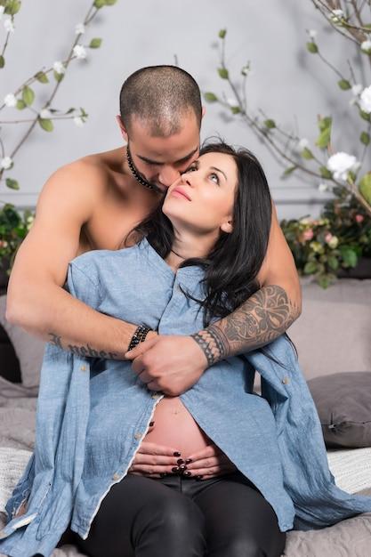 Joli Couple International D'homme à La Poitrine Nue Serrant Sa Femme Enceinte Brune Assise Sur Un Lit Douillet Gris Dans La Chambre Photo Premium