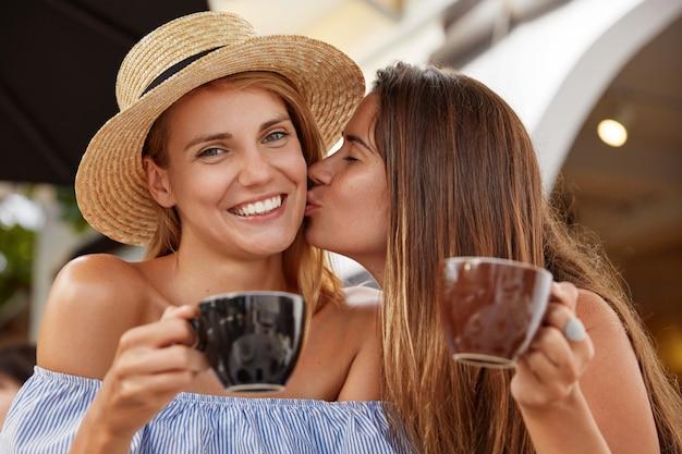 Un Joli Couple De Lesbiennes Boit Du Café à La Cafétéria Extérieure, Apprécie La Convivialité, S'embrasse, A Un Large Sourire. Belle Femme Heureuse De Recevoir Le Baiser De Sa Petite Amie. Amour Mutuel. Photo gratuit