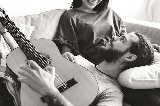 Joli couple sur un petit ami de canapé jouant un concept de musique et d'amour de guitare Photo gratuit