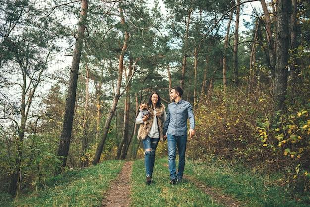 Joli Couple Avec Petit Yorkshire Terrier Marchant Dans La Forêt. Photo Premium