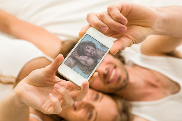 Joli Couple Prenant Un Selfie Allongé Sur Son Lit Photo Premium