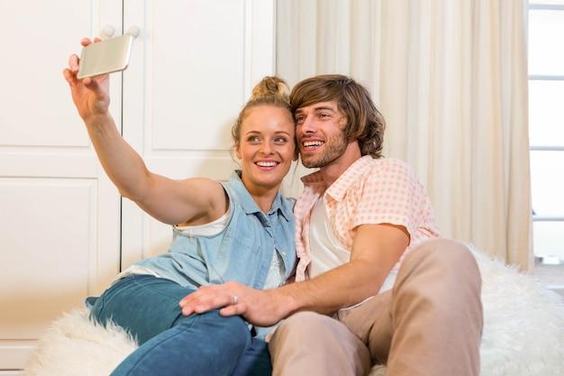 Joli couple prenant un selfie avec smartphone dans le salon Photo Premium