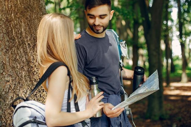 Joli couple se reposer dans une forêt en été Photo gratuit