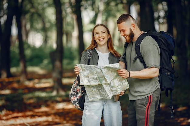 Joli couple se reposer dans une forêt Photo gratuit