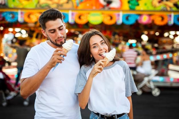 Joli couple en train de manger des glaces au salon Photo gratuit
