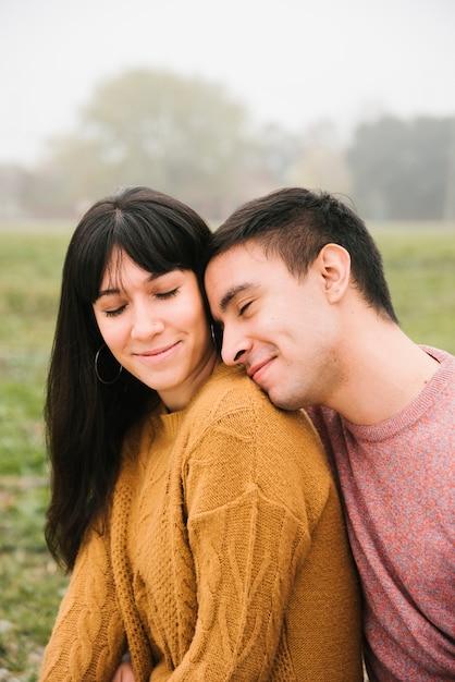 Joli couple yeux fermés souriant et embrassant dans le parc Photo gratuit