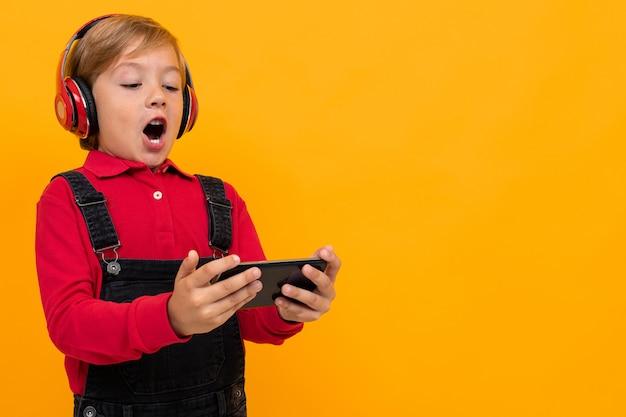 Joli Enfant écouter De La Musique Et Regarder Un Film Avec Un Smartphone Photo Premium