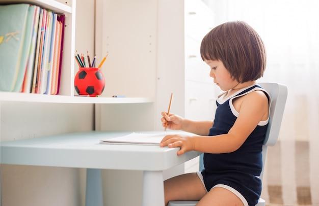 Joli enfant souriant faisant ses devoirs, coloriant des pages, écrivant et peignant Photo Premium