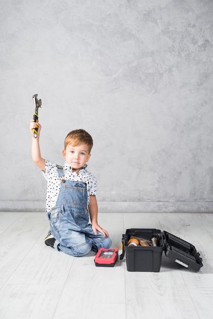 Joli garçon assis avec une clé Photo gratuit
