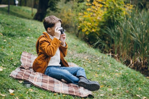 Joli garçon marche et pose dans un parc d'automne coloré Photo Premium