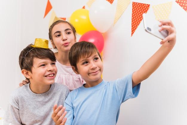 Joli garçon prenant selfie avec ses amis sur un téléphone intelligent Photo gratuit