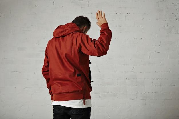 Un Joli Jeune Homme En Veste Rouge Vagues Portrait Au Revoir De L'arrière Sur Un Mur Blanc Photo gratuit