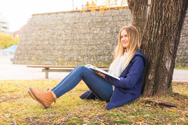 Joli modèle assis arbre incliné et lecture Photo gratuit
