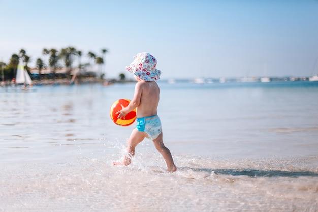 Joli petit bébé frisé joue avec une balle colorée sur la plage. petite fille marchant sur l'eau au bord de la mer. Photo Premium