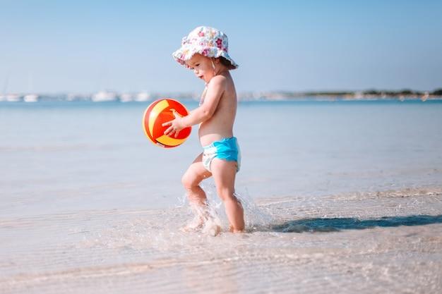 Joli petit bébé frisé joue avec un ballon coloré sur la plage Photo Premium