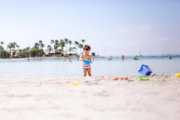 Joli petit bébé frisé joue avec de l'eau et du sable sur la plage au bord de la mer. Photo Premium
