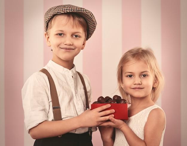 Joli Petit Couple Tenant Une Boîte Avec Praline Photo gratuit