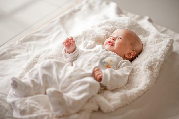 Joli petit garçon dans une chambre à la lumière blanche le nouveau-né est mignon. dans la literie pour les enfants nés - images Photo Premium