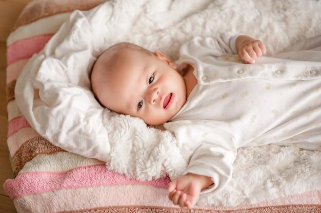 Joli petit garçon dans une chambre à la lumière blanche le nouveau-né est mignon. Photo Premium
