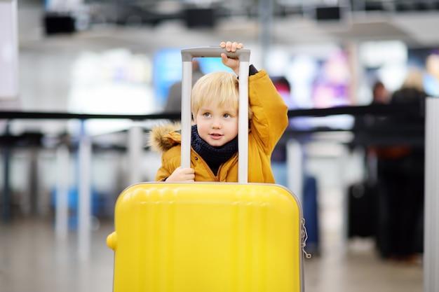 Joli petit garçon avec une grosse valise jaune à l'aéroport international avant le vol Photo Premium
