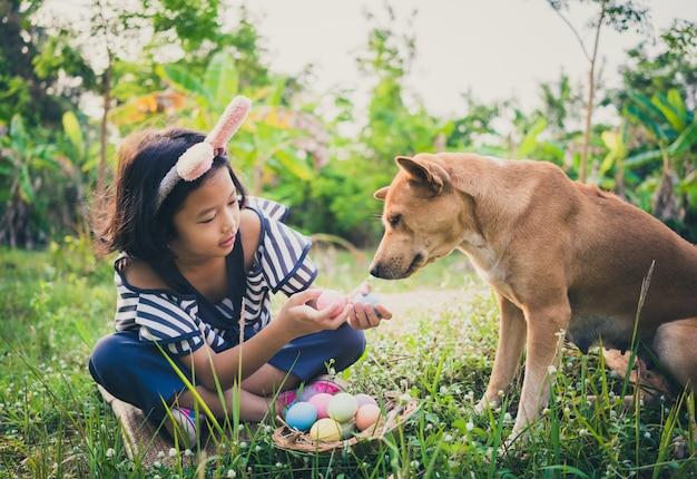 Joli petit gril portant des oreilles de lapin avec des oeufs de pâques et son chien. Photo Premium