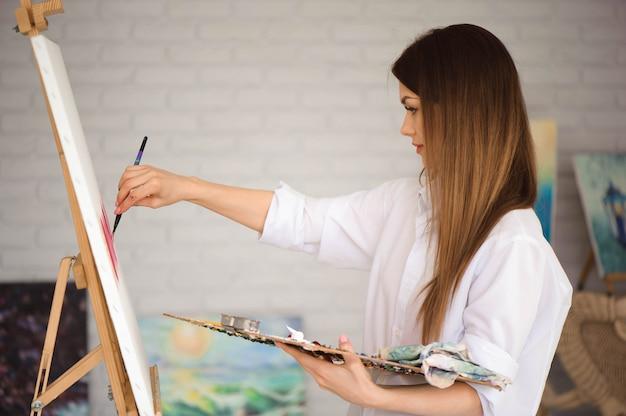 Jolie artiste belle fille peindre une image sur une toile sur un chevalet. Photo Premium