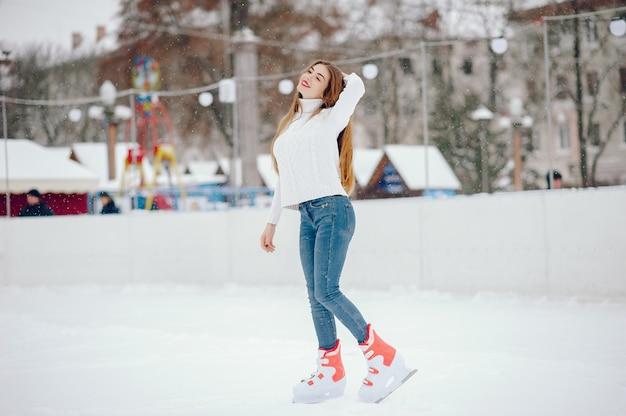 Jolie et belle fille dans un pull blanc dans une ville d'hiver Photo gratuit