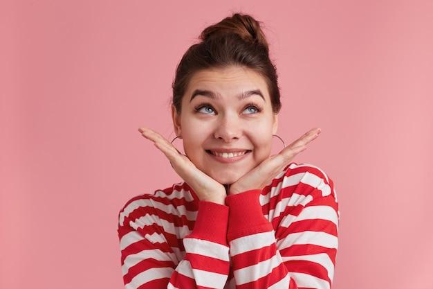 Jolie Belle Jeune Femme Avec Des Taches De Rousseur Regarde De Côté, Garde Les Deux Mains Sur Les Joues, Habillée En T-shirt Rayé Sur Rose Photo gratuit