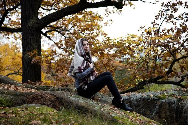 Une jolie, belle et modeste fille de religion avec un foulard ou un foulard sur la tête est assise à l'automne dans un parc sur une pierre. Photo Premium