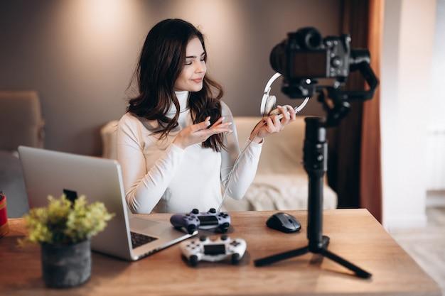 Jolie Blogueuse Filme Et Montre Sa Préférence Dans Les écouteurs Pour Les Jeux Vidéo. Influenceuse Jeune Femme En Direct En Streaming. Photo Premium