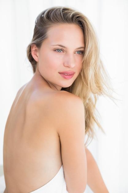 Jolie blonde assise sur une table de massage Photo Premium